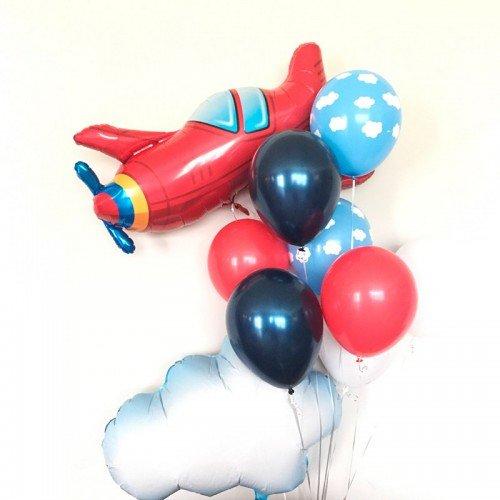 Фонтан шаров с красным самолетом в облаках